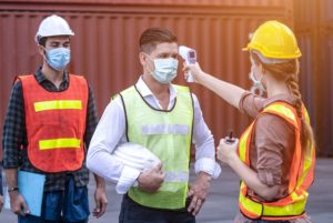 Woman in hardhat doing temp checks on two men with hardhats and COVID masks